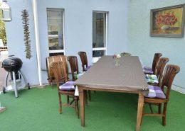 Großes überdachte Terrasse mit Tisch, Stühlen und Kugelgrill.