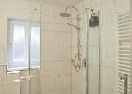 Badezimmer 1 mit Fenster, Dusche, WC, großem Spiegelschrank, Kosmetikspiegel und Föhn.