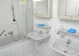 Badezimmer 2 mit Badewanne, Duschwand, zwei Waschbecken mit Spiegelschränken - und im Vorraum ein WC mit zusätzlichem Waschbecken.