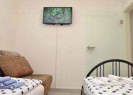 Schlafzimmer 3 mit einem Einzelbett und Schlafsofa sowie Flachbildschirm-TV. Der dazugehörige Kleiderschrank wird in Kürze im Flur vor dem Zimmer aufgebaut.