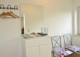 Geräumiger Eingangsbereich mit separater Garderobe, Schuhablage, Schrank mit großem Spiegel, Fenster und zwei Stühlen.